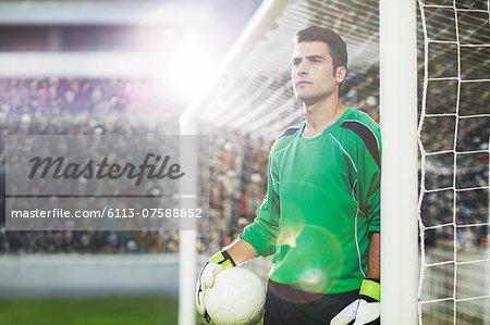 Goalie holding ball on soccer field