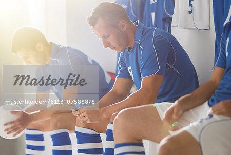Soccer players sitting in locker room
