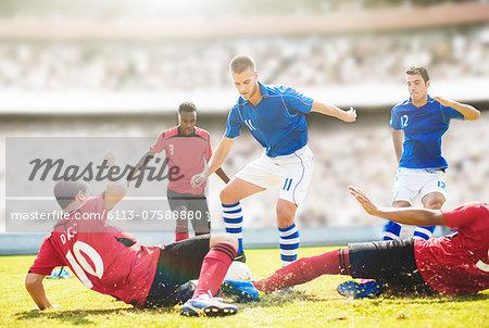 Soccer players sliding on field