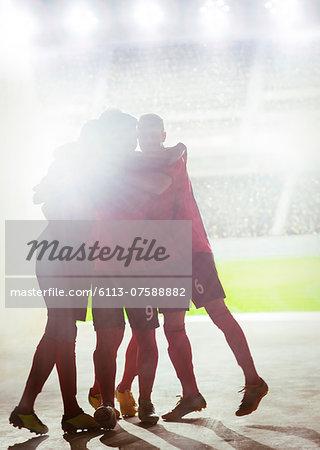 Silhouette of soccer team celebrating