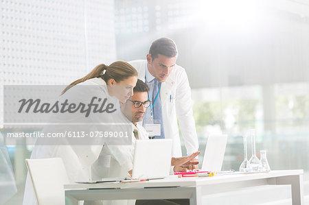 Doctors using laptop in laboratory