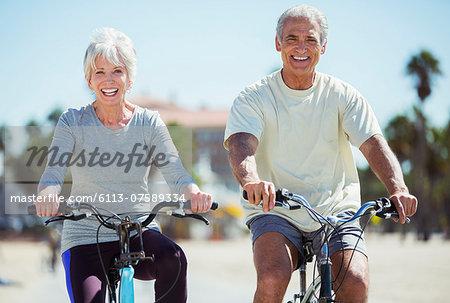Portrait of senior couple riding bicycles on beach