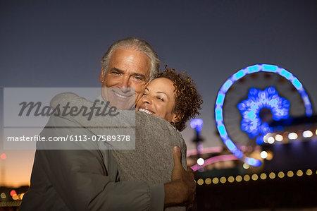 Portrait of couple hugging outside amusement park at night
