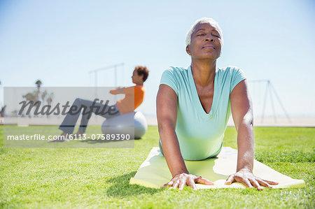 Women practicing yoga in sunny park