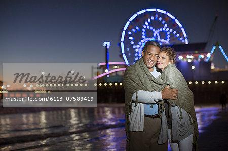Couple hugging on beach at night