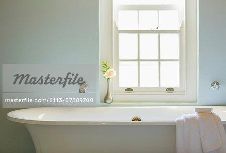 Soaking tub below window in luxury bathroom