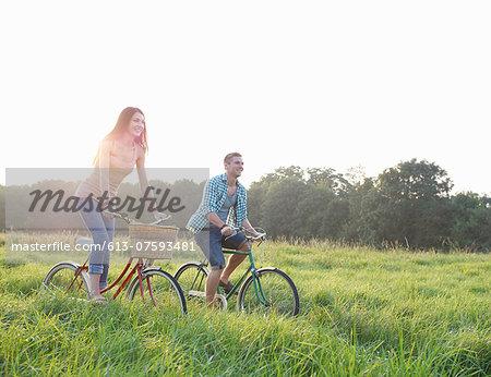 Couple riding bikes through Summer meadow.