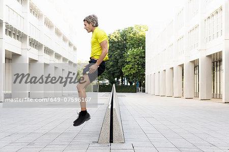 Mature man jumping over divider