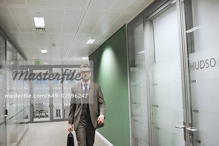Confident mature businessman walking along office corridor
