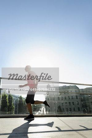 Runner crossing bridge, Munich, Germany