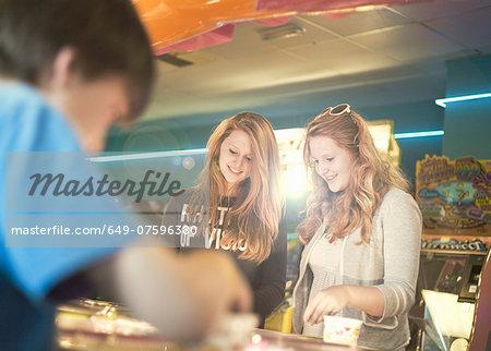 Teenage sisters playing games in amusement arcade