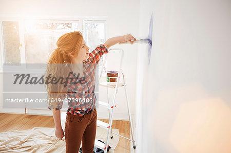 Teenage girl painting her bedroom wall