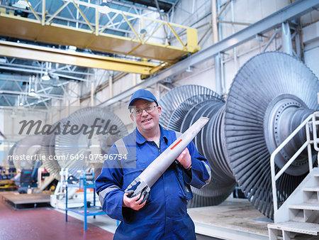 Portrait of engineer holding rotor blade in turbine repair workshop