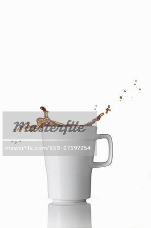 Black coffee splashing out of the mug