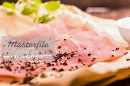 Sliced ham with black pepper