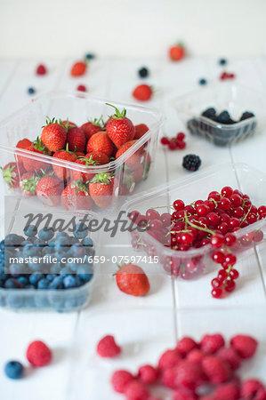 blueberries, blackberries, raspberries, strawberries, redcurrants on a white table