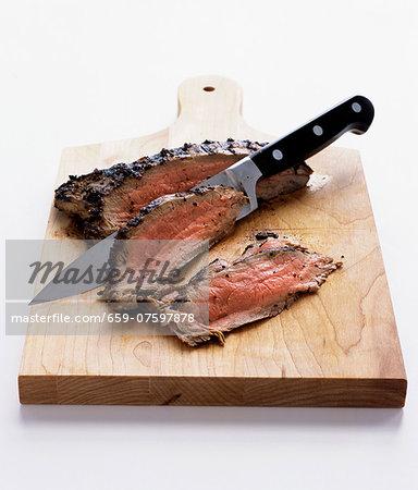Sliced roast beef on a chopping board