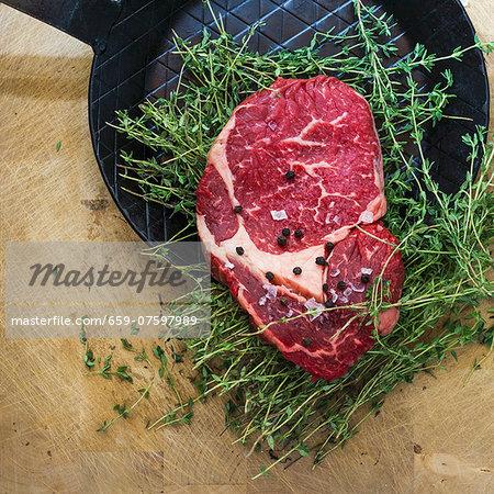 Rib eye steak with thyme on a black frying pan