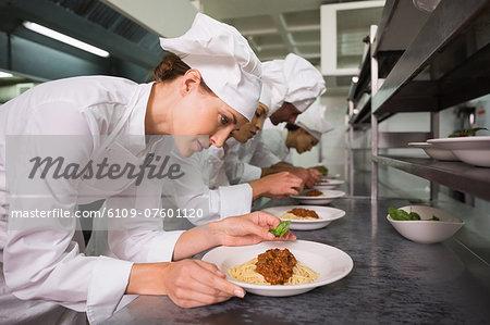 Row of chefs garnishing spaghetti dishes with basil leaf