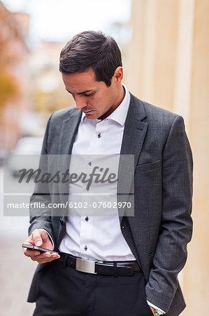 Mid adult businessman using cell phone, Stockholm, Sweden