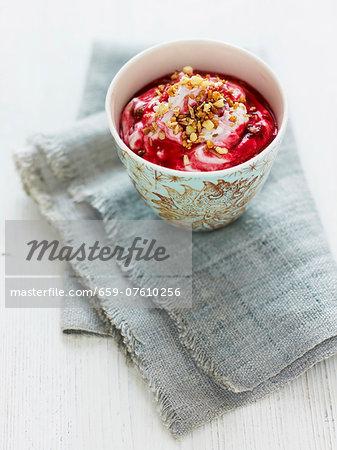 Yogurt with raspberry coulis and chopped hazelnuts