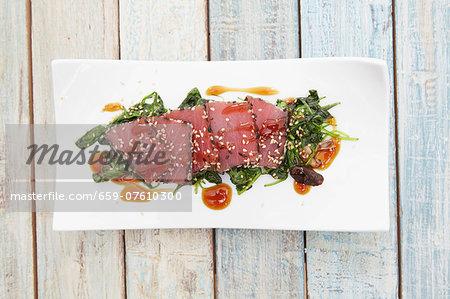 Tuna sashimi with sesame on a bed of seaweed