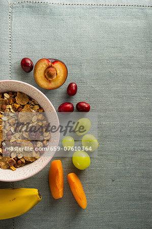 A bowl of muesli next to fresh fruit
