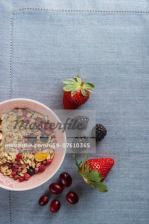 A bowl of muesli next to fresh berries