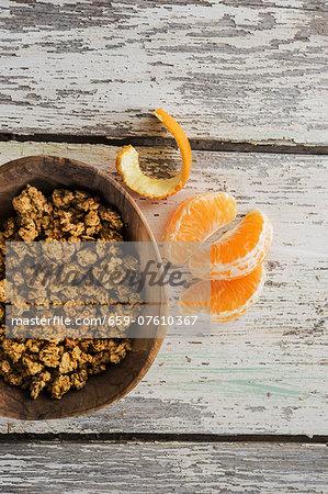 A bowl of crunchy muesli next to mandarin segments