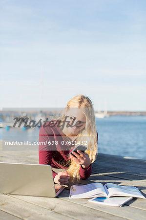 Happy high school girl using mobile phone on pier