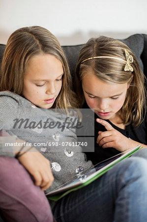 Siblings using digital tablet together on sofa