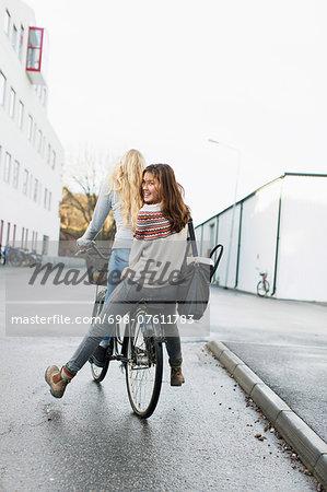 Teenage girls riding bicycle on high school campus