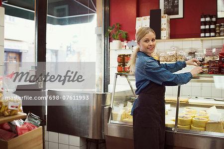 Side view portrait of confident saleswoman standing working in supermarket