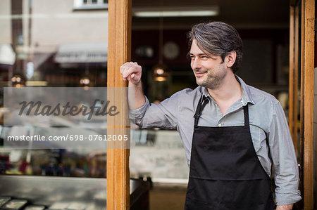 Thoughtful salesman looking away at supermarket entrance
