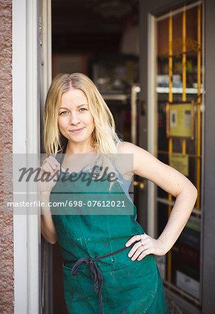 Portrait of confident fashion designer standing at studio doorway