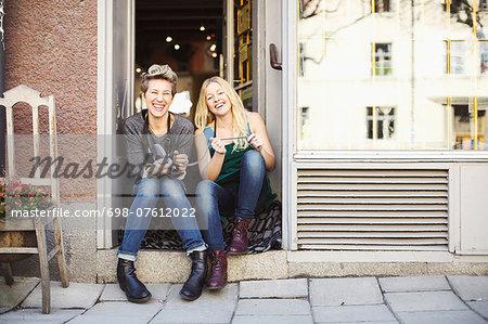 Full length portrait of female tailors sitting at studio doorway