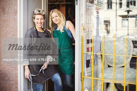 Portrait of confident fashion designers at studio doorway