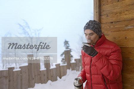 Man enjoying hot drink from flask