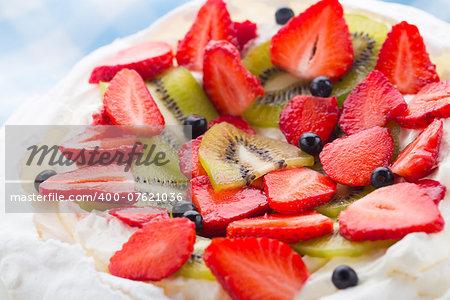 Pavlova cake with strawberry, kiwi and blueberries