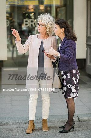 Full length senior women searching direction on digital tablet at city street