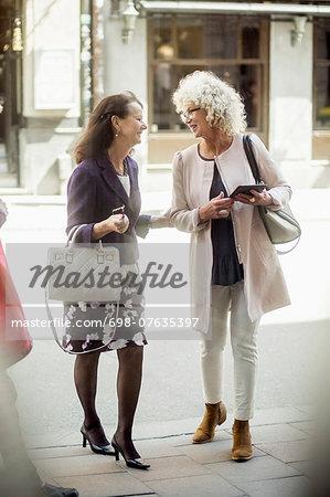 Happy senior female friends talking while walking on street
