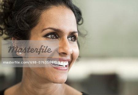 Happy businesswoman looking away in office
