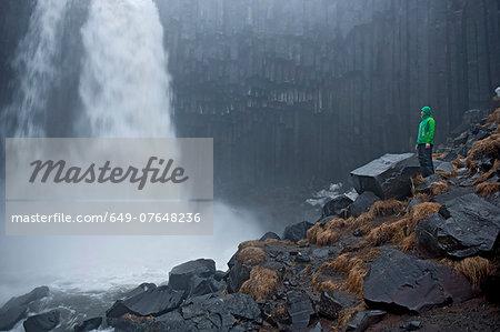 Mature woman gazing at the Svartifoss waterfall at Skaftafell, Vatnajokull National Park, Iceland