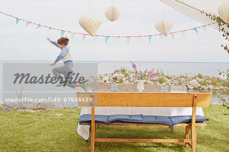 Young boy jumping mid air at party