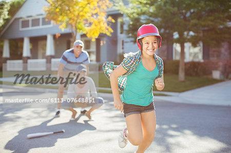 Family playing baseball in street