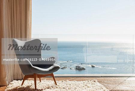 Chair in sunny window overlooking ocean