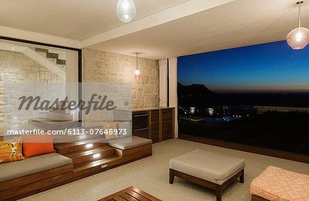 Luxury living room overlooking ocean at night