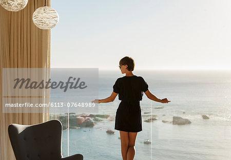Woman standing at balcony railing overlooking ocean