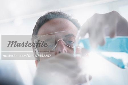 Scientist pouring liquid into test tube