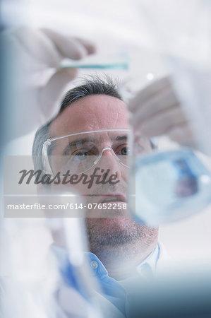 Scientist pouring liquid into measuring beaker